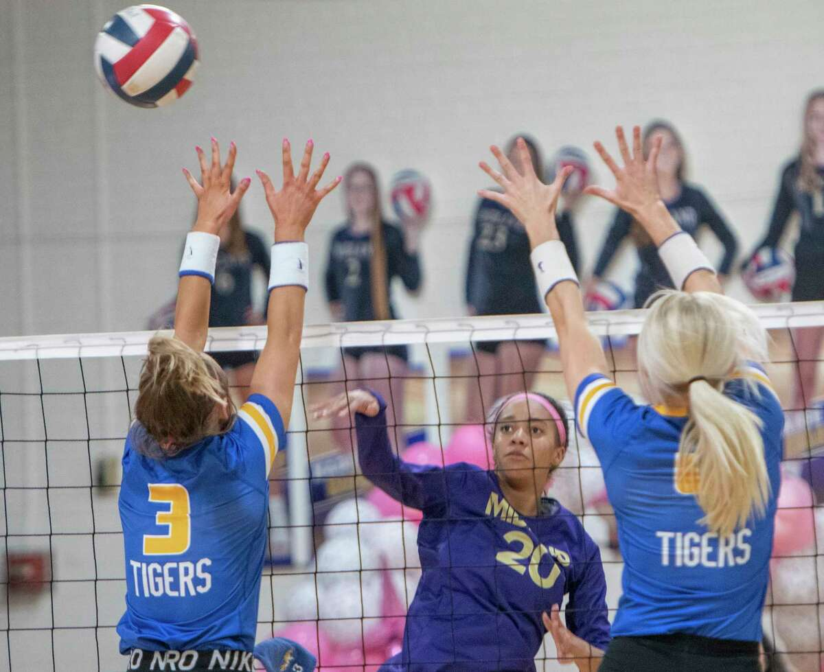 Midland High's Kaylee Day tips the ball past the reach of Frenship's Devyn Nairn and Lexi Moore 10/12/2021 at the Midland High gym. Tim Fischer/Reporter-Telegram
