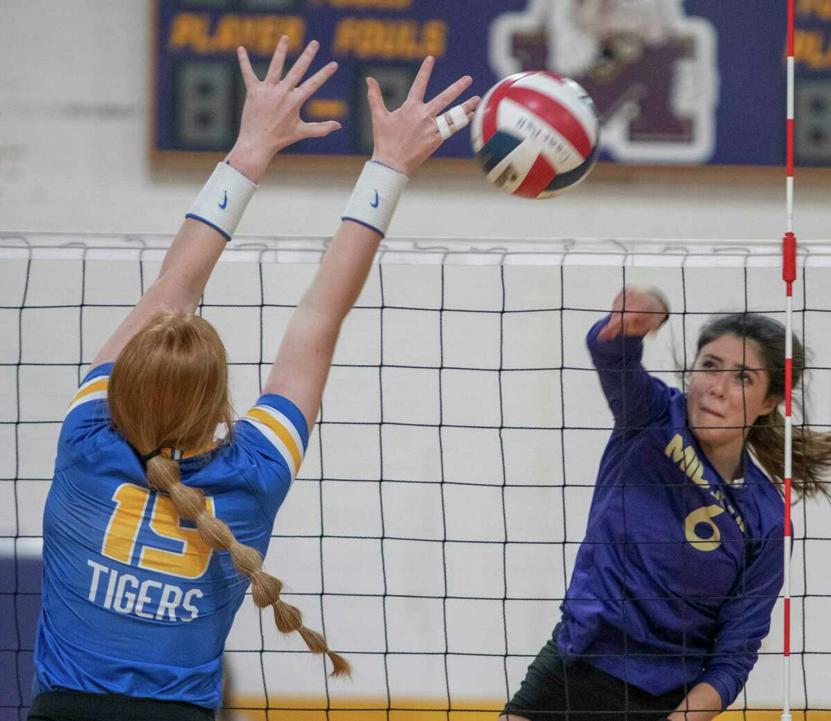 Midland High's Jamie Swisher gets the kill down the line away from the block of Frenship's SouthernAnn Cox 10/12/2021 at the Midland High gym. Tim Fischer/Reporter-Telegram