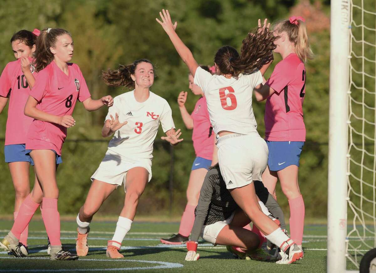 New Canaan's Dillyn Patten (3) and Kaleigh Harden (6) celebrate a first-half goal during the Rams' girls soccer game against Darien in Darien on Tuesday, Oct. 12, 2021.