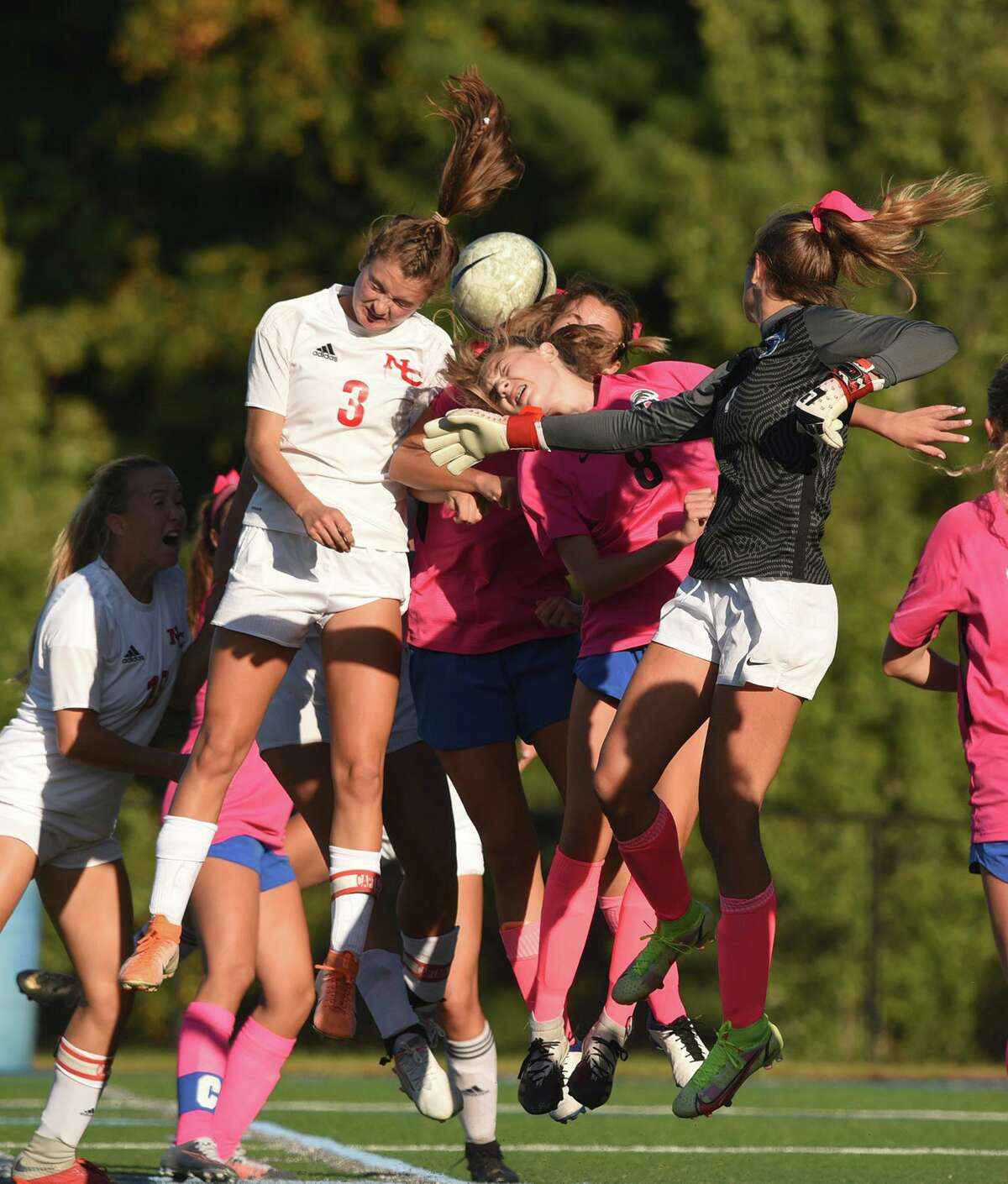 New Canaan's Dillyn Patten (3) and Darien's Caroline Aponte (8) and goalie Jillian Fox take to the air on a corner kick during a girls soccer game in Darien on Tuesday, Oct. 12, 2021.