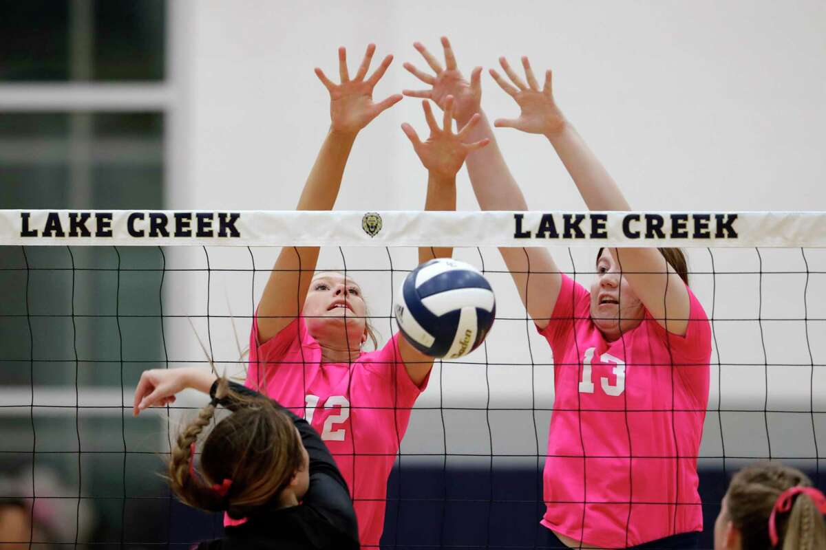 Lake Creek's Grace Ellis (12) and Anna Ertischek (13) block a spike from Montgomery during their regular season District 20-5A volleyball match at Lake Creek High School Tuesday, Oct. 12, 2021 in Houston, TX.