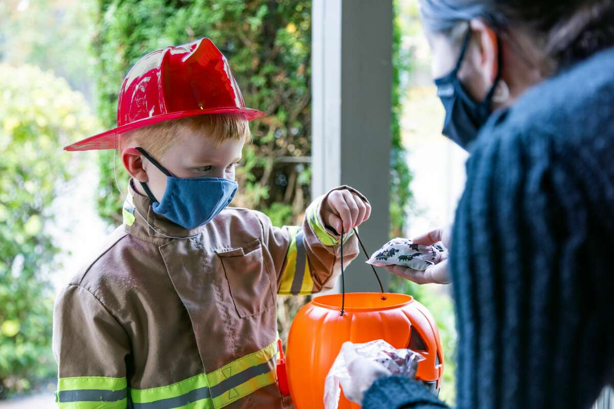 Young boy wearing firefighter costume receives candies on Halloween. A young woman is giving candies at the front door and they are both wearing protective mask.
