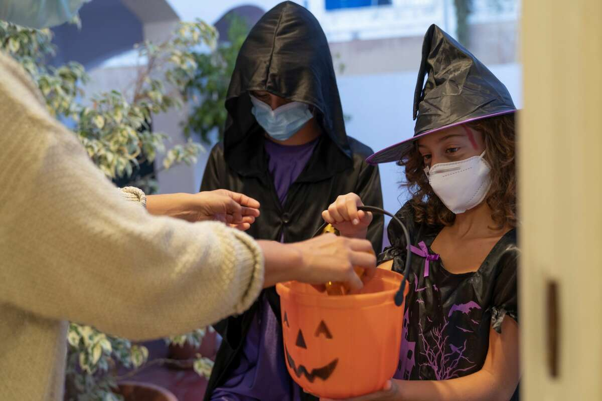 Children dressed in Halloween costumes trick-or-treating with face masks.