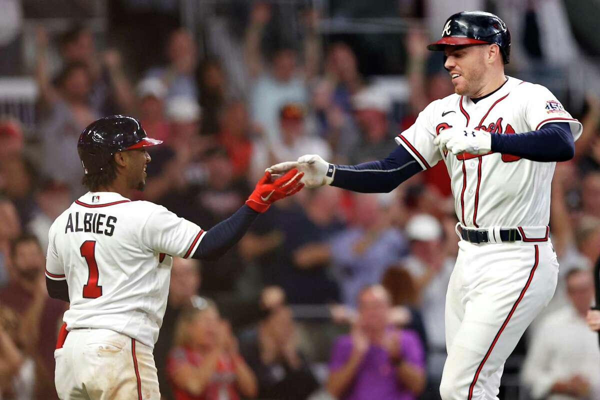 ATLANTA, GEORGIA - OCTOBER 12: Freddie Freeman #5 of the Atlanta Braves celebrates with Ozzie Albies #1 after hitting a home run during the eighth inning against the Milwaukee Brewers in game four of the National League Division Series at Truist Park on October 12, 2021 in Atlanta, Georgia. (Photo by Todd Kirkland/Getty Images)