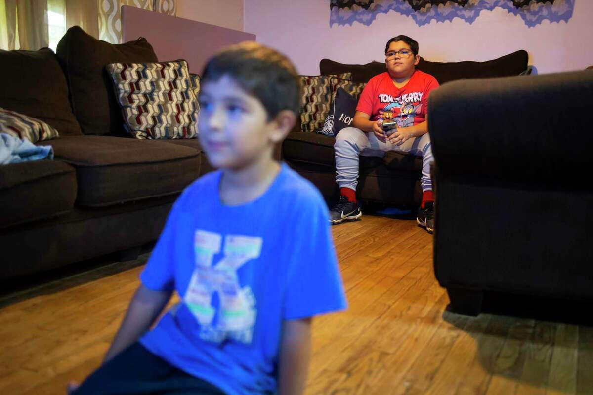 Jacen Thornton, right, watches a MTS music video with his younger brother James in their home in Houston on Tuesday, Oct. 12, 2021.