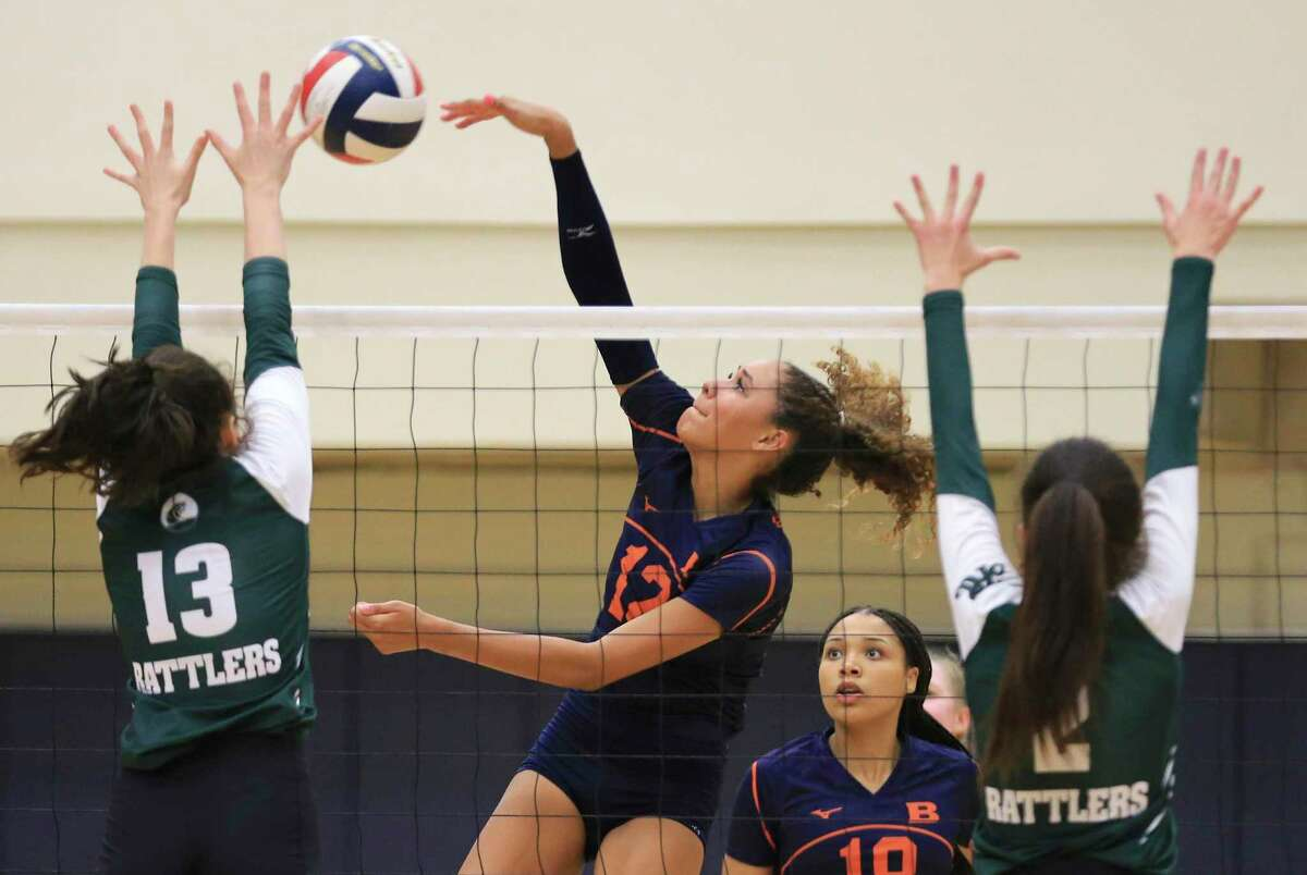 Brandeis' Jalyn Gibson (12) goes for one of her 21 kills against Reagan's Katie Hill (13) and Megan Fitch (02) during their volleyball game at Paul Taylor Fieldhouse on Tuesday, Oct. 12, 2021. The Broncos prevailed, 3-1 in sets, to take the night's win.