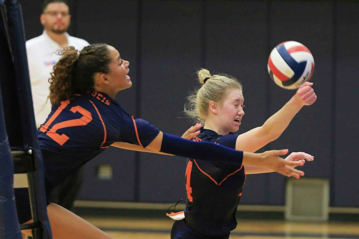 Brandeis' Emma Halstead (right) and Jalyn Gibson (12) scramble to make a save during their volleyball game against Reagan at Paul Taylor Fieldhouse on Tuesday, Oct. 12, 2021. The Broncos prevailed, 3-1 in sets, to take the night's win.