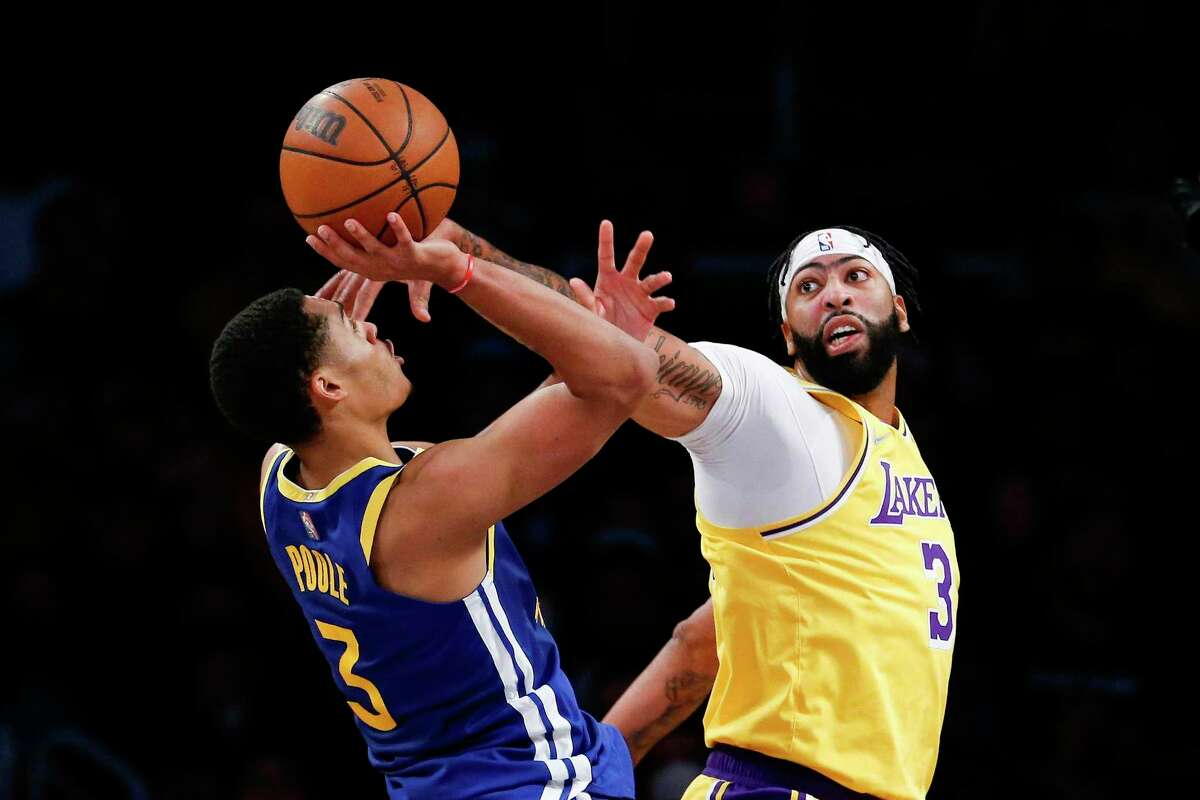Golden State Warriors guard Jordan Poole, left, shoots under pressure from Los Angeles Lakers forward Anthony Davis during the first half of a preseason NBA basketball game in Los Angeles, Tuesday, Oct. 12, 2021. (AP Photo/Ringo H.W. Chiu)