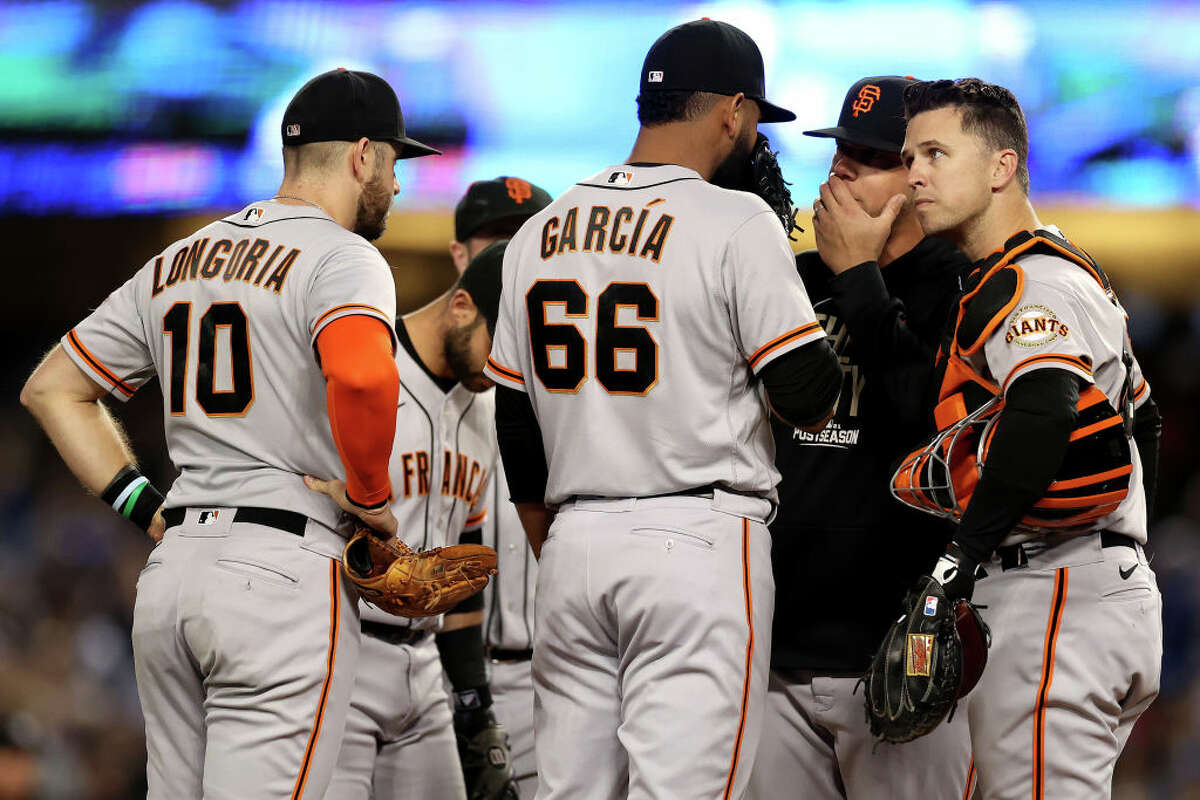 Pitching coach Andrew Bailey talks with Jarlin Garcia of the San Francisco Giants.