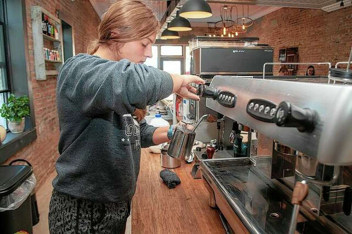 Tristan Lashmett steams milk for a coffee at Rural Cyclery in Winchester. Along with bicycle repairs, the cycling shop also offers craft beers and coffees.
