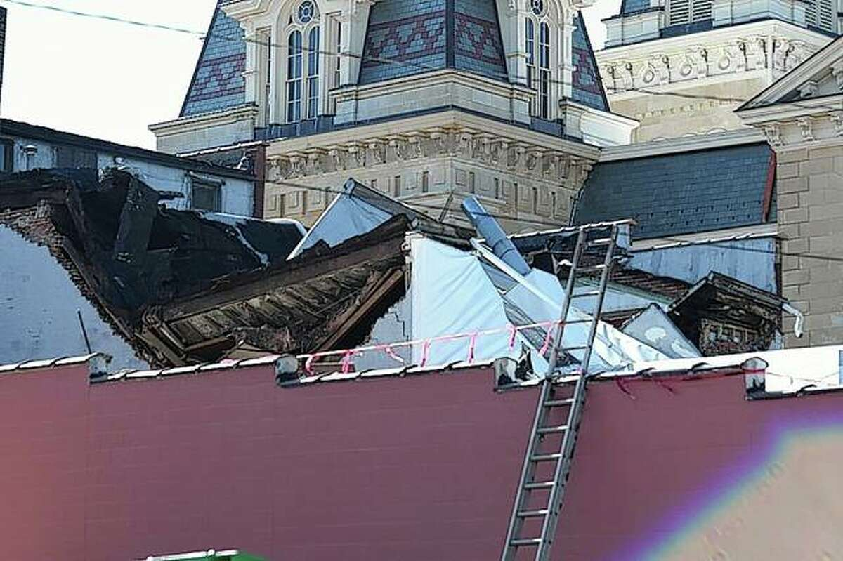 A roof lies collapsed Tuesday morning at a building at 102½ and 104 N. West St. The portion of North West Street between East State and Court streets is closed until further notice because of the unstable structure.