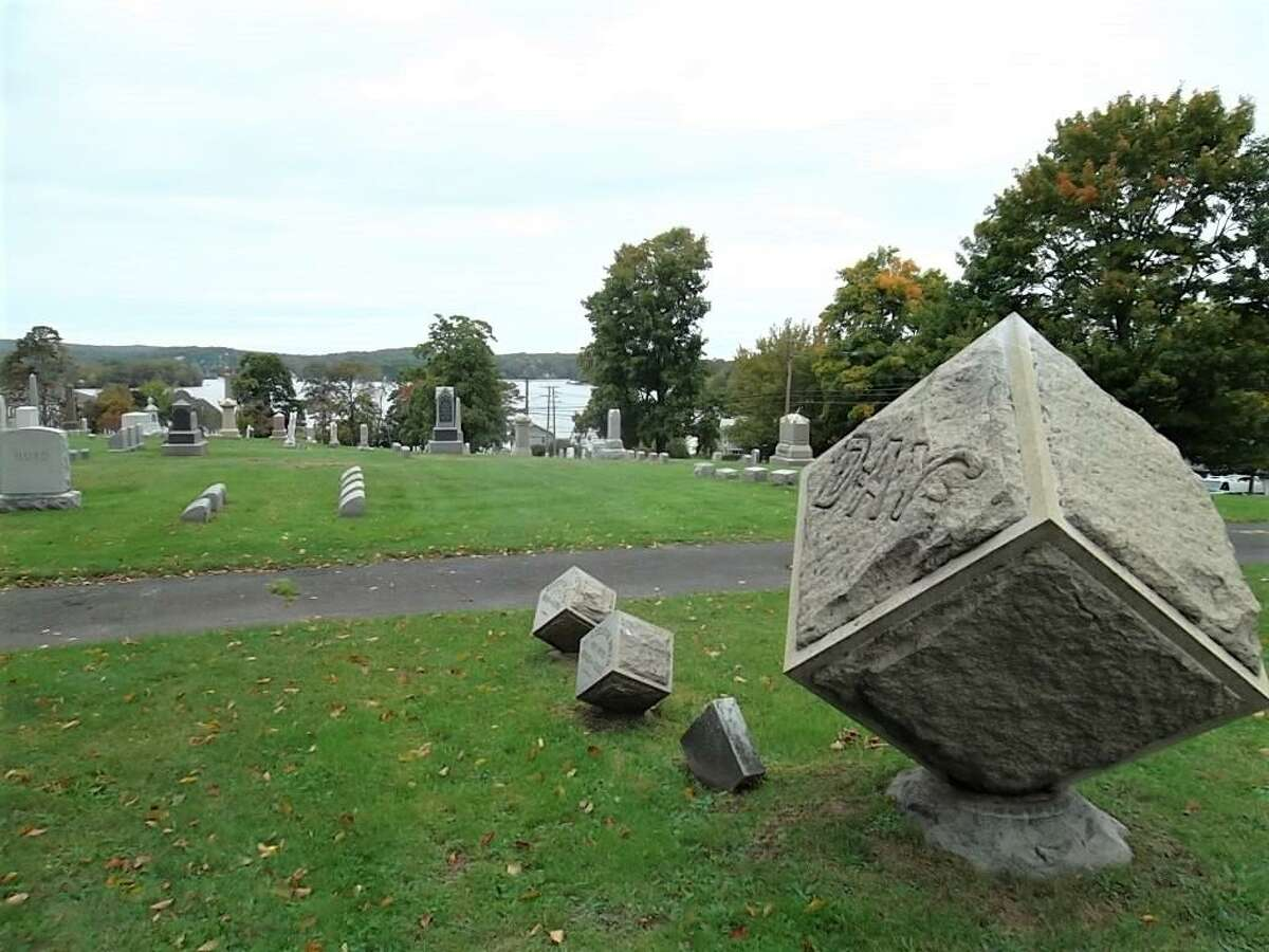 Shown here are gravestones at Lake View Cemetery in East Hampton, with Lake Pocotopaug in the background.