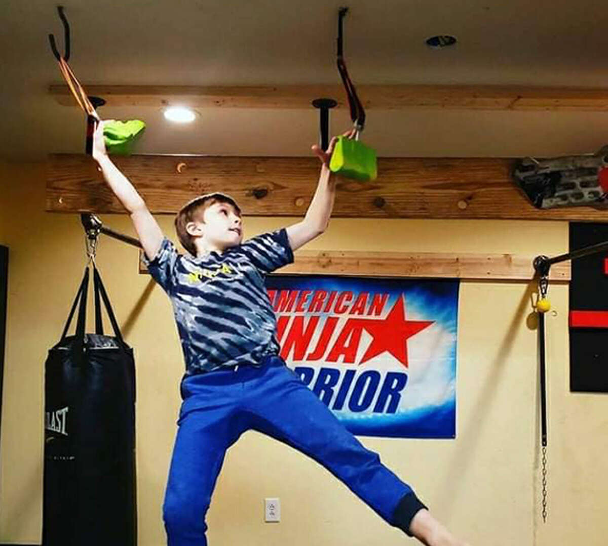 """Colton Davis, 9, of Edwardsville, does ninja training in the basement of his home. He will appear in Thursday's episode of """"American Ninja Warrior Junior,"""" which will be streamed on the Peacock network."""