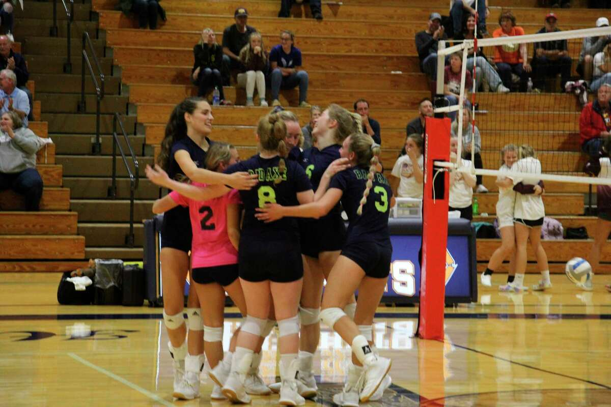 The Lady Hatchets celebrate after winning the first set. (Tom Greene/Huron Daily Tribune)