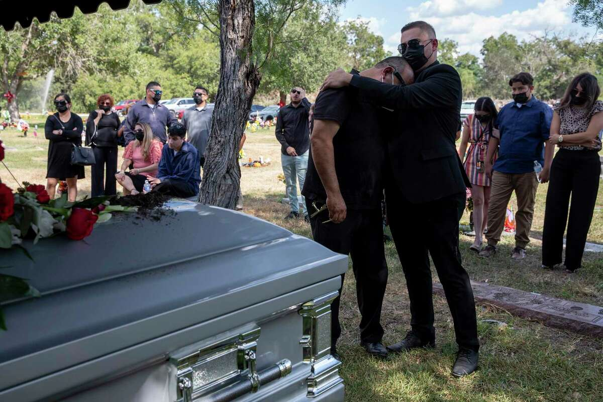 Sergio Gonzalez is comforted by a family member after the coffin of his wife, Veronica, was lowered into the ground. She is among the more than 4,600 Bexar County residents who have died from COVID-19.