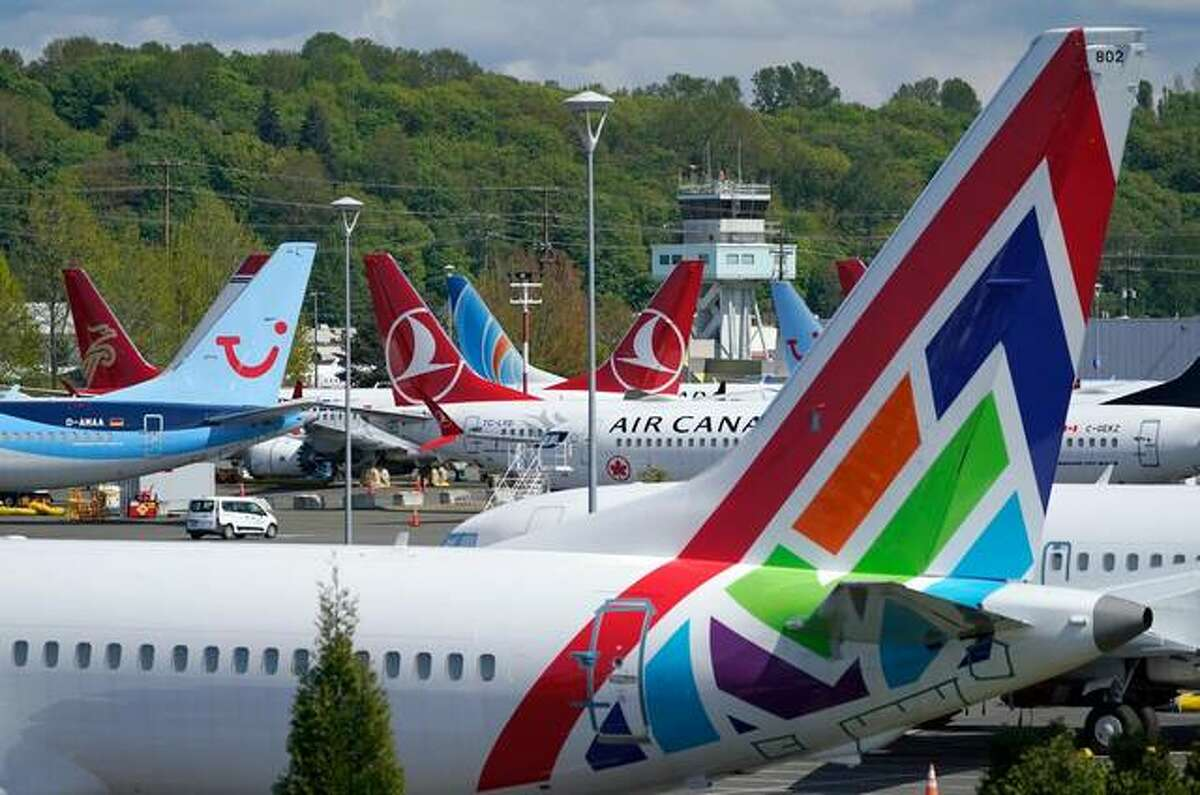 In this April 26, 2021, file photo Boeing 737 Max airplanes sit parked in a storage lot, near Boeing Field in Seattle. The Boeing Co. told employees, Tuesday, Oct. 12, 2021, that they must be vaccinated against COVID-19 or possibly be fired. The Seattle Times reports the deadline for workers at the aerospace giant is Dec. 8.
