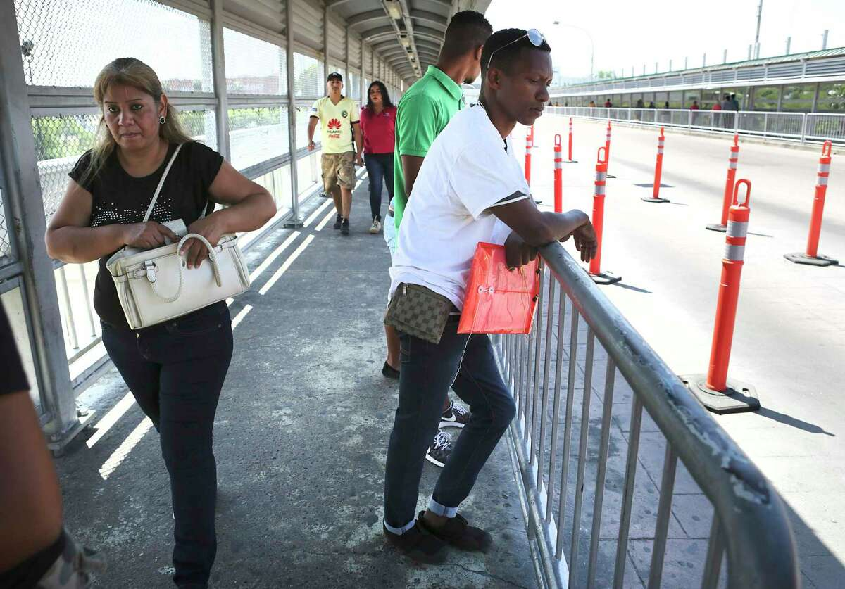 Mexicans cross the international bridge from Nuevo Laredo to Laredo, Texas, left, passing a couple of Cuban immigrants, center, who were stopped by U.S. Customs and Border Protection agents who walked the Cubans back to Mexico, on Saturday, April. 8, 2017.