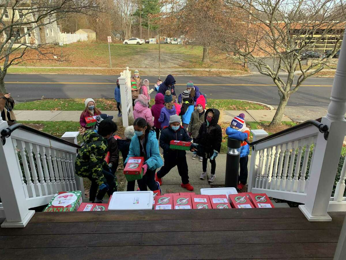 Ridgefield High School senior Sean O'Hara, center, is rallying community members to participate in Operation Christmas Child for the second year in a row. Pictured, students from St. Mary's School drop off packed shoeboxes to O'Hara's home in 2020.
