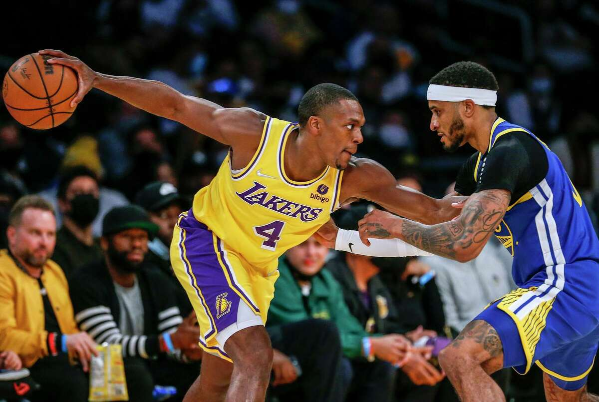 Los Angeles Lakers guard Rajon Rondo, left, is defended by Golden State Warriors guard Gary Payton II during the second half of a preseason NBA basketball game in Los Angeles, Tuesday, Oct. 12, 2021. (AP Photo/Ringo H.W. Chiu)