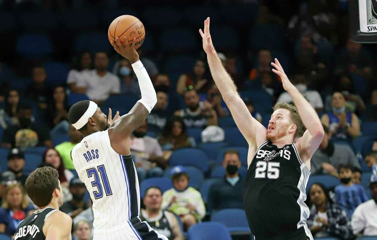 Orlando Magic forward Terrence Ross (31) floats a shot over Spurs center Jakob Poeltl (25) during the second half of a preseason game on Sunday, Oct. 10, 2021, in Orlando, Fla.