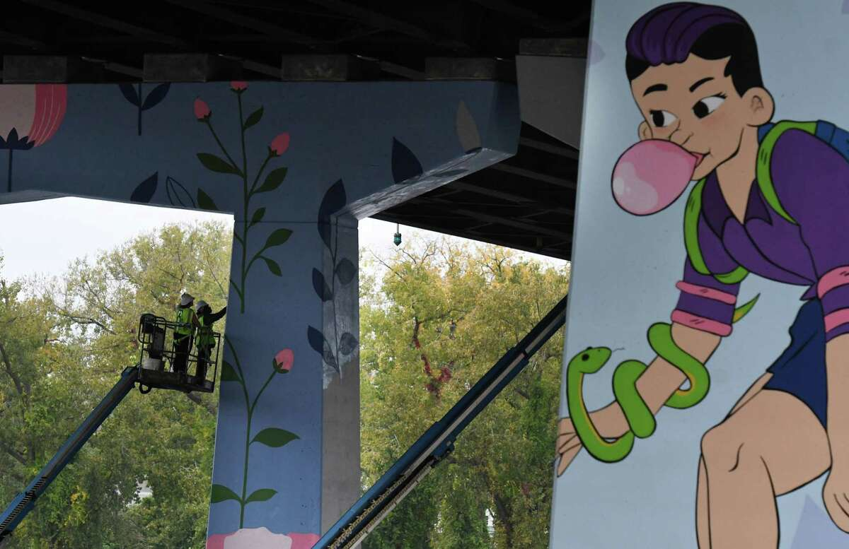 Artists add to the Uniting Line project mural under Collar City Bridge on Wednesday, Oct. 13, 2021, on Hoosick Street in Troy, N.Y. The project is a collaboration between The Arts Center of the Capital Region and the city of Troy. The massive murals were designed by local artist Jade Warrick and sponsored primarily by a $25,000 grant from Bloomberg Philanthropies.