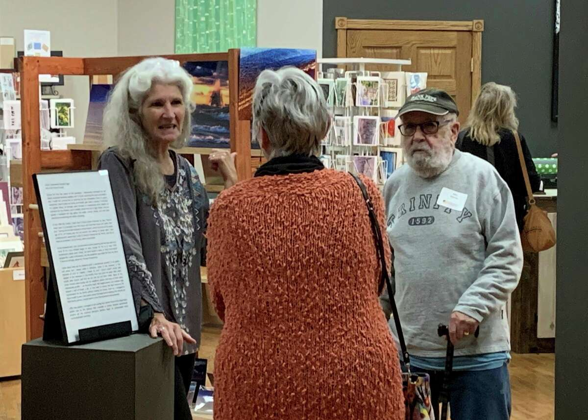 """Big Rapids artist Kym Nicolas (left) speaks about her art installation """"Love and Loss in the Time of Corona, Phase 1 and Phase 2."""" Artists will be on hand Thursday evening during the reception for Artworks new exhibit """"Art in the Time of COVID."""" (Pioneer photo/Julie Norwood)"""
