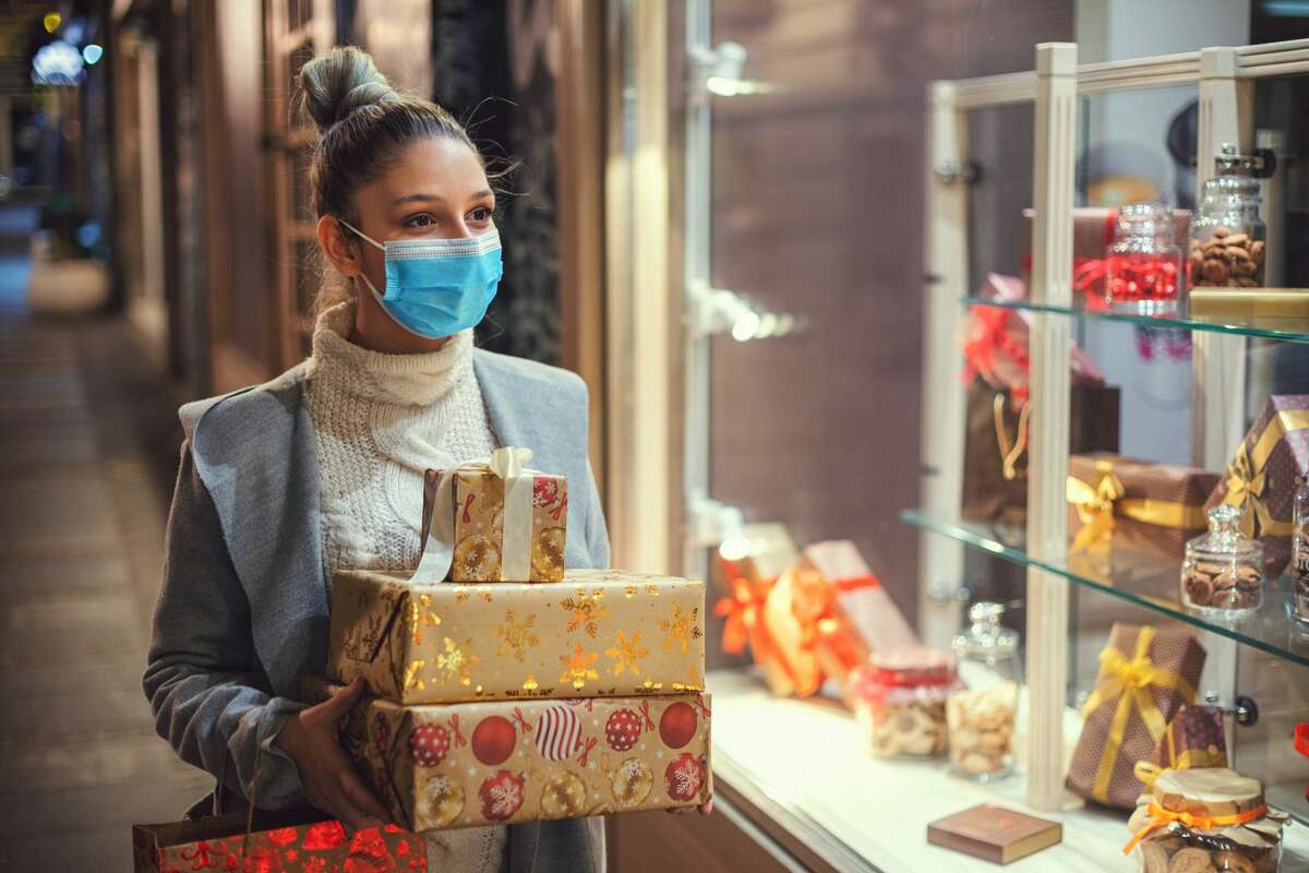 Pictured is a woman walking and shopping Christmas gifts in the city.
