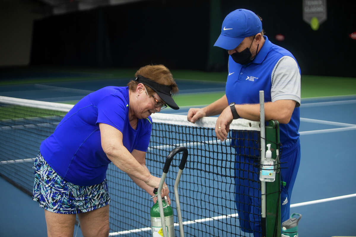 Holly Wedding of Birch Run, left, connects a longer tube to her oxygen tank before beginning her weekly tennis training session with Mike Andrews, right, Tuesday, Oct. 12, 2021 at the Greater Midland Tennis Center. Wedding, a longtime tennis player, recovered early this year from a very serious case of COVID-19, and is back on the court as part of her rehabilitation. (Katy Kildee/kkildee@mdn.net)