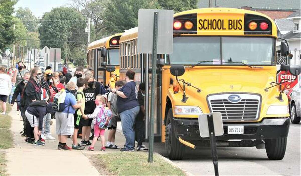 Buses load in front of Lewis and Clark Elementary School in Wood River Wednesday afternoon. The Wood River-Hartford School District currently has three rotating buses driver, but is only using two for the new schedule.