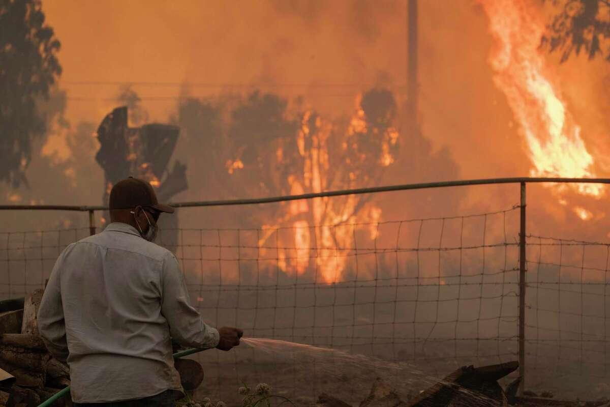 A ranch hand sprays water with a hose as the Alisal Fire burns on Tuesday near Goleta in Santa Barbara County.