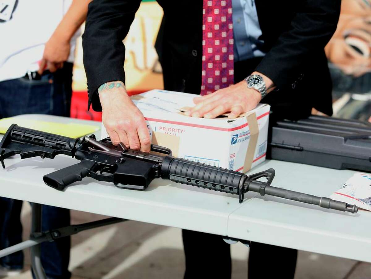 An inspector with the San Francisco District Attorney's Office displays a ghost gun during a news conference at the United Playaz Violence Prevention Program on Tuesday.