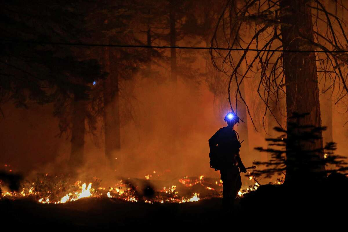 The Caldor Fire burns near a home in the El Dorado County community of Strawberry in August. California's fire season is stretching into November, research shows.