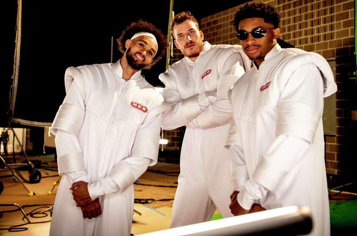 Derrick White, from left, Jakob Poeltl and Keldon Johnson pose in space suits for a new round of the Spurs' popular H-E-B commercials.