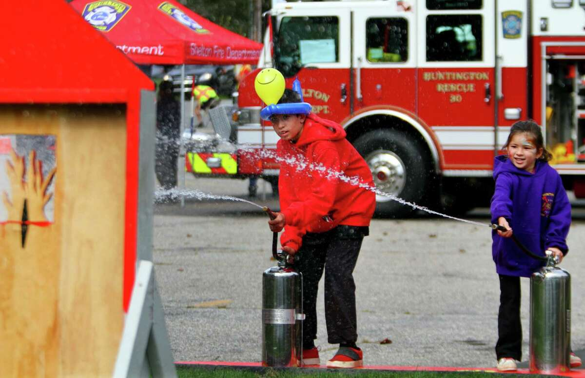 """Joseph Fittante, 11, and his sister Giovanna, 4, use a water supplied fire extinguiser to try an knock over """"flames"""" during Huntington Fire Company No. 3's first ever fire prevention event in Shelton on Saturday. A variety of activities were available for kids to take part in. Kids learned valuable fire safety tips from department firefighters, got a close up view of life-saving equipment and face paintings to name just a few."""