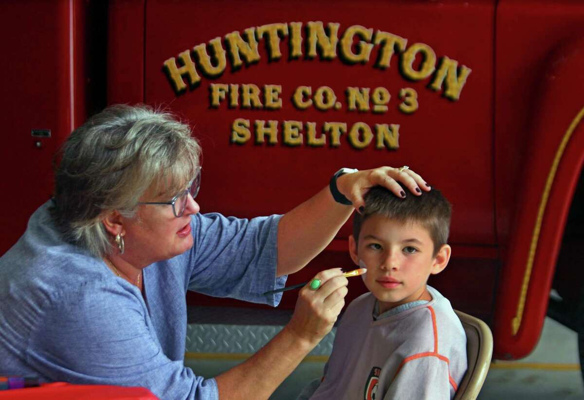 Andrew Fittante, 9, gets his face painted by Kelly McClinch Pineau.
