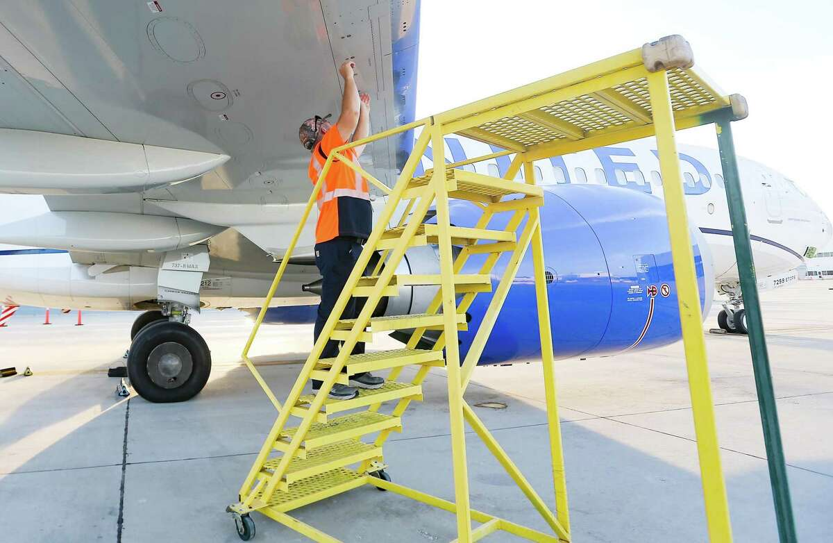 A United Airlines mechanic opens the fuel tank before a test flight with 100 percent sustainable aviation fuel in Houston on Wednesday, Oct. 13, 2021. The airline is hoping to have its whole fleet be sustainable in 2050.