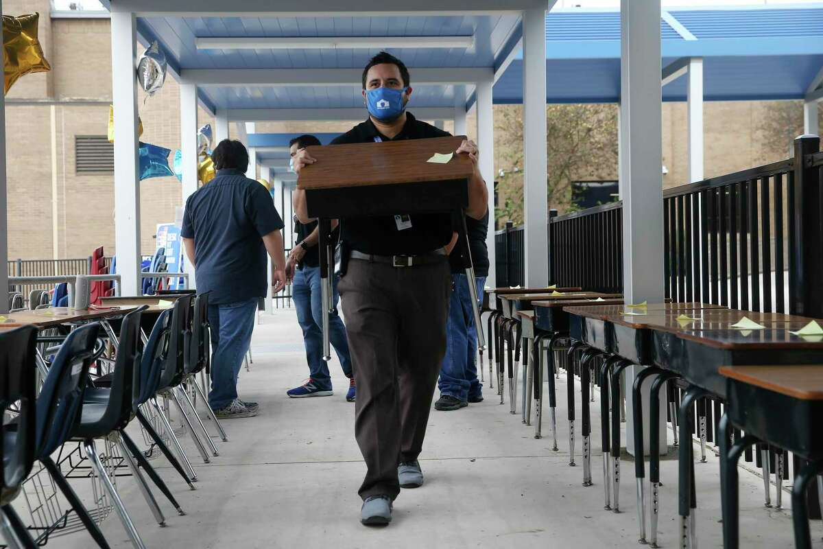 Fourth-grade math teacher Rudy Villa carries a desk to a family picking up for students studying remotely at J.T. Brackenridge Elementary School Friday, Nov. 20, 2020. The school gave away 75 desks to around 50 families. The desks are outgoing inventory that is being replaced by monies from San Antonio ISD's Bond 2016.