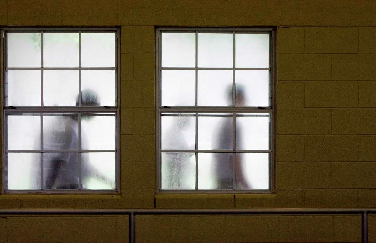 Youths walk by the windows of the dining hall on their way to lunch Thursday, Oct. 12, 2006, at the Giddings State School in Giddings, Texas. Giddings State School is a juvenile detention facility east of Austin serving time with the Texas Youth Commission for a variety of crimes including aggravated assault, sexual assault, car theft to capital murder. (Photo by Brett Coomer / Houston Chronicle) Contact: Tim Savoy (512) 351-0952