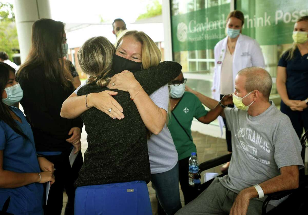 Florida residents Susan and Robby Walker hug medical staff during Robby's release from Gaylord Hospital and Covid-19 treatment in Wallingford on Wednesday.