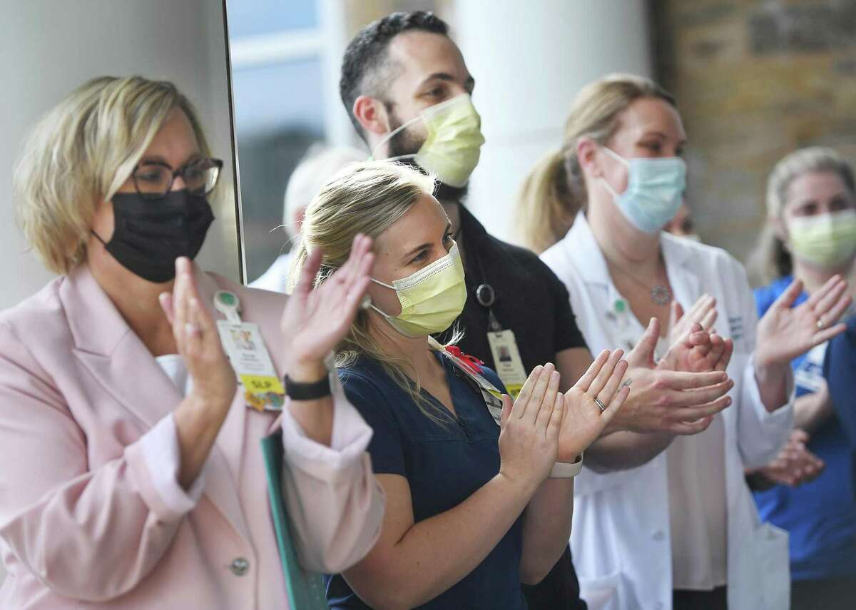 Medical staff applaud the release of Florida resident Robby Walker from Covid-19 rehabilitation at Gaylord Hospital in Wallingford, Conn. on Wednesday, October 13, 2021.