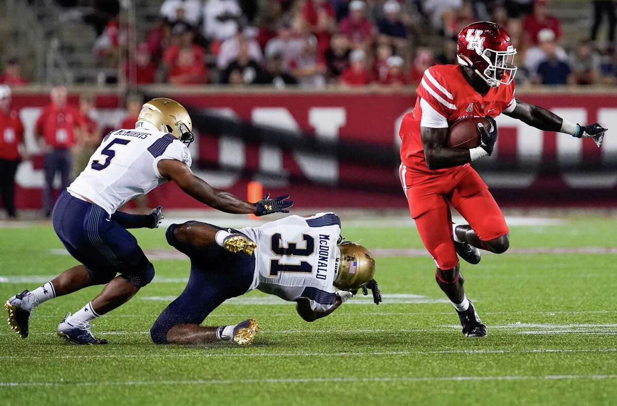 Houston Cougars running back Alton McCaskill strikes a familiar pose as he evades a pair of Navy defenders.