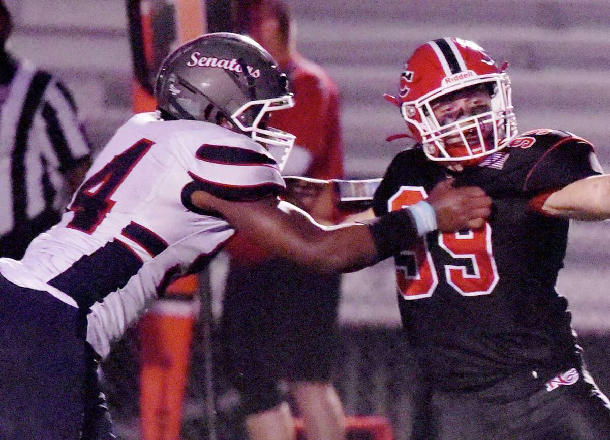 Brien McMahon's Isaiah Epps (54) battles New Canaan's Dillon Blair (99) during a game at Dunning Field in New Canaan on Sept. 17.