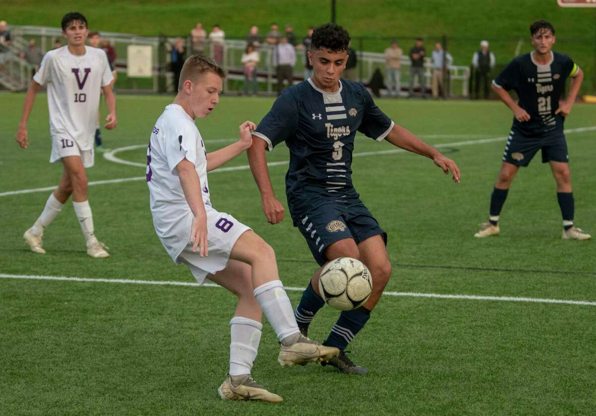 Voorheesville's Jake Johnson, left, kicks the ball past Cohoes' Johnny Martinez-Peraza during the Colonial Council tournament boys' soccer game on Wednesday, Oct, 13, 2021 in Troy, N.Y.