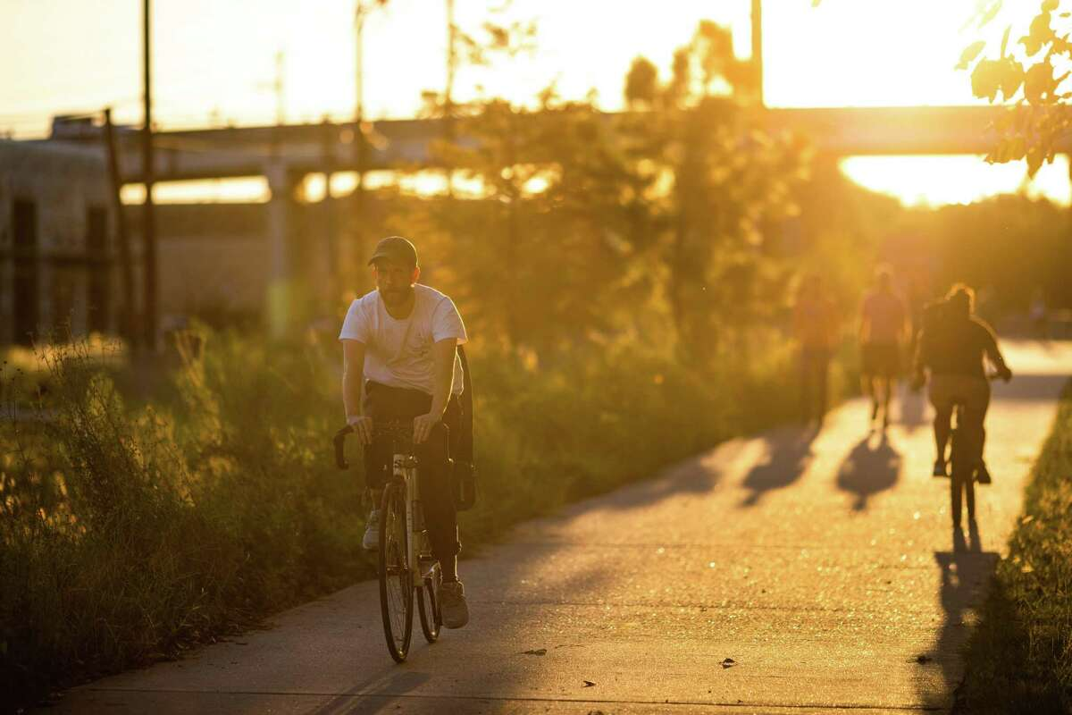 People ride bicycles on a hike and bike trail by M-K-T, a trail-oriented, mixed-use, project at North Shepherd Dr., Thursday, Sept. 23, 2021, in Houston.