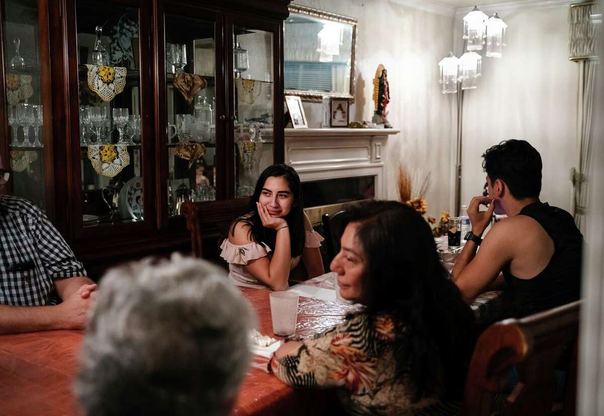 Eighteen-year-old Jessica Ramos listens to her family speak at the dinner table at her grandmother's home in Hayward.