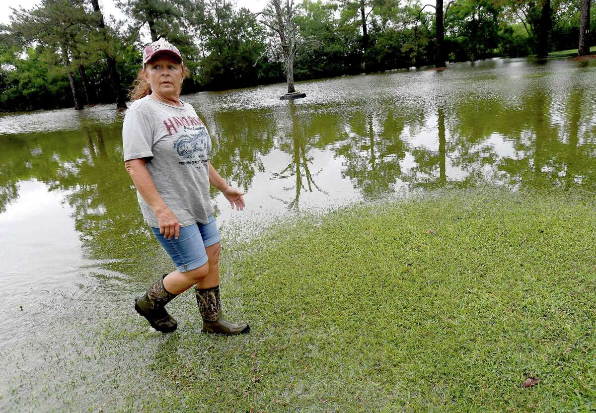Julie Meadows walks through the flooded yard of her home on West Clubb Road in Fannett Tuesday. The area received over a foot of rainfall Monday, flooding area bayous and several yards and homes. This is the third time Meadows' home has flooded, and she believes a drainage ditch at the back of her property, which is overgrown and has been neglected for years, is largely to blame. Photo made Tuesday, May 18, 2021 Kim Brent/The Enterprise