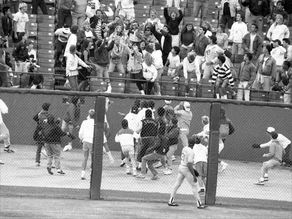 July 26, 1988: Los Angeles Dodgers outfielder John Shelby watch as rowdy fans cluster around a Giants home run in a game between the two rivals. Giants fans brawled and threw batteries on the field and 30 fans were arrested.