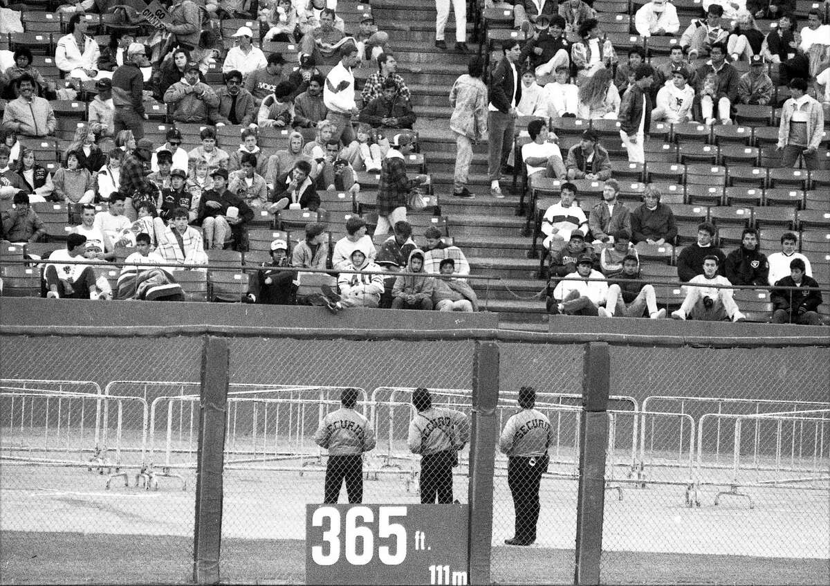 Security guards watch fans behind barricades during a Giants game against the Dodgers at Candlestick Park on July 26, 1988.