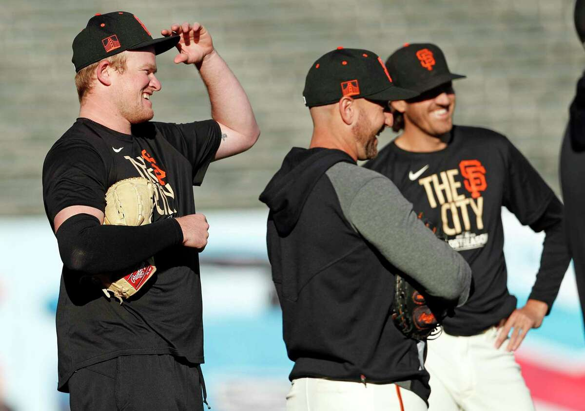 San Francisco Giants' Logan Webb (left) and Kevin Gausman (right) laugh with teammates during workout before Game 5 of NLDS at Oracle Park in San Francisco, Calif., on Wednesday, October 13, 2021.