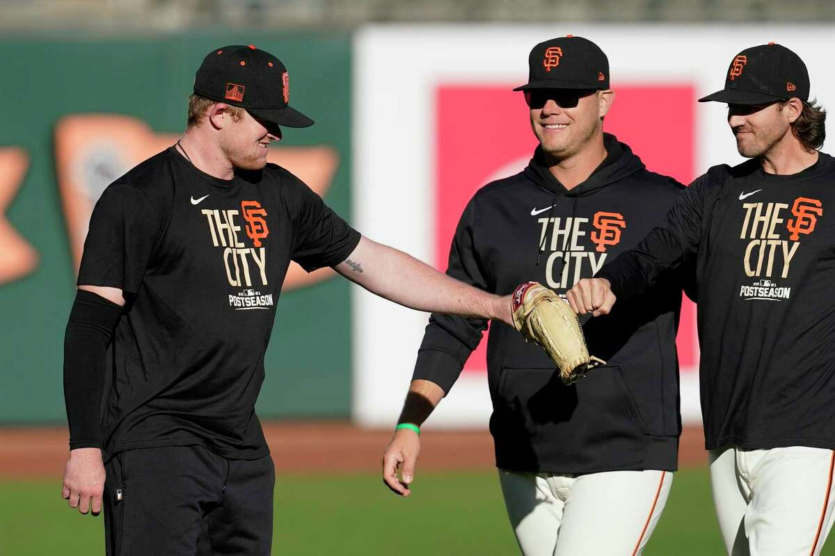San Francisco Giants pitcher Logan Webb, left, greets pitcher Kevin Gausman, right, during baseball practice Wednesday, Oct. 13, 2021, in San Francisco. The Giants are scheduled to play the Los Angeles Dodgers in Game 5 of a National League Division Series on Thursday. (AP Photo/Jeff Chiu)
